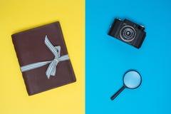 Gammalt anteckningsbok, kamera och förstoringsglas Arkivfoton