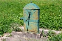 Gammalt använde sällan den rostade utomhus- metallvattenpumpen med det stora roterande handtaget som monterades på konkret ställn royaltyfri bild