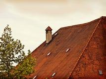 Gammalt bayerskt tak med röda tegelplattor och lampglaset Arkivbild