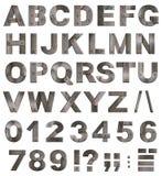gammalt belägga med metall alfabetet märker, siffror, interpunktion Fotografering för Bildbyråer