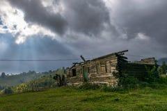 Gammalt bränt och övergett hus i ett berglandskap Arkivbilder