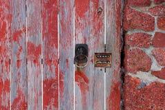 Gammalt brunt dörrhandtag och kombinationslås på trägrå röd dörr och humana staketbräden royaltyfri foto