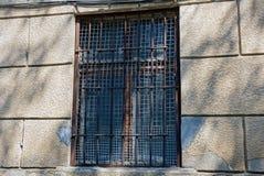 Gammalt brunt fönster bak stänger på en grå betongvägg fotografering för bildbyråer