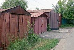 Gammalt brunt järn parkera bilen i garage i busksnåren av gräs nära vägen Royaltyfri Bild