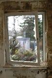 Gammalt brutet fönster med en sikt till yttersidan arkivfoto