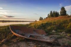 Gammalt brutet fartyg på kusten av sjön på solnedgången _ Arkivbild