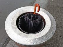 Gammalt brutet paraply i fack för ett gataavfall på en regnig dag Royaltyfria Bilder