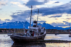 Gammalt brutet skepp som ashore strandas, och by med berg Royaltyfri Fotografi