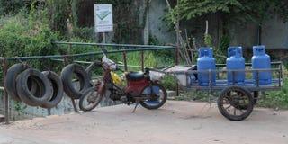 Gammalt brutet som vara nedst?md med en vagn som det finns tre bl?a gasflaskor p? Typisk transport arkivbilder