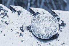 Gammalt bultat silvermynt som är utsatt på en skyffel som finnas i livpik arkivbild