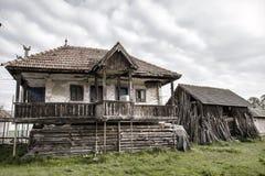 Gammalt bygdhus och en gammal ladugård i en rumänsk by Arkivfoto