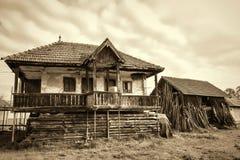 Gammalt bygdhus och en gammal ladugård i en rumänsk by Royaltyfri Bild