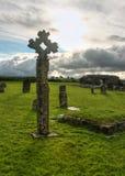 Gammalt celtic stenkors på kyrkogård mycket av grönt gräs royaltyfria bilder