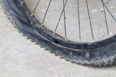 Gammalt cykelhjul med det plana däcket på vägen Royaltyfria Foton