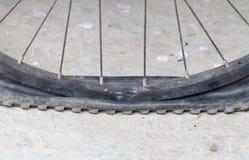 Gammalt cykelhjul med det plana däcket på vägen Royaltyfri Bild