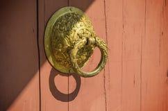 Gammalt dörrhandtag på den wood dörren och solljus royaltyfria bilder