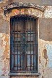 Gammalt dammigt fönster med rostiga stänger royaltyfri bild