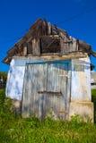 Gammalt degraderat hus under blå himmel Arkivfoton