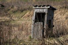 Gammalt desintegrera träbås med den sönderrivna dörren i gräs royaltyfri fotografi