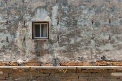 Gammalt fönster i en forntida vit tegelstenvägg Royaltyfri Fotografi