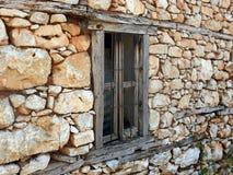 Gammalt fönster i en stenvägg Arkivbild