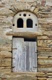 Gammalt fönster i en stenvägg royaltyfria bilder