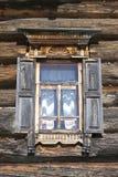 Gammalt fönster med öppna slutare som är glass med en blå himmel på bakgrunden av träväggen av bygdjournalhuset Arkivbild