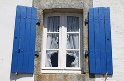 Gammalt fönster med det blåa träskyddet Arkivbild