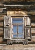 Gammalt fönster med exponeringsglas med en blå himmel på bakgrunden av träväggen av bygdjournalhuset Arkivbild