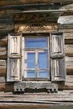 Gammalt fönster med exponeringsglas med en blå himmel på bakgrunden av träväggen av bygdjournalhuset Royaltyfria Bilder