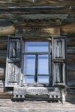 Gammalt fönster med exponeringsglas med en blå himmel på bakgrunden av träväggen av bygdjournalhuset Arkivfoton