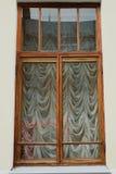 Gammalt fönster med gardiner utanför arkivfoto