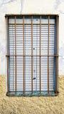 Gammalt fönster med säkerhetsstänger, stålgaller royaltyfri foto