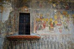 Gammalt fönster och en målad kyrklig vägg Relegious kyrkakonst royaltyfri bild