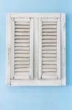 Gammalt fönster på blåttskyväggen Royaltyfri Bild