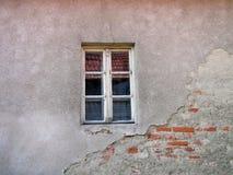 Gammalt fönster på den skadade tegelstenväggen med sprickor Arkivfoto