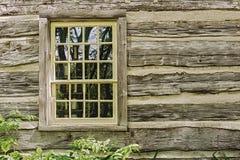 Gammalt fönster på en trälantgårdhusvägg Arkivfoto