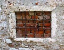 Gammalt fönster som blockeras med spisgallrar och tegelstenar Royaltyfri Bild