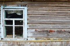 Gammalt förfallet fönster av ett träbyhus och en vägg av den förfallna journalen Fotografering för Bildbyråer