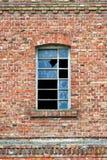 Gammalt fabriksfönster med brutet exponeringsglas Royaltyfri Bild
