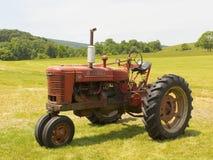 Gammalt Farmall traktorsammanträde i ett fält royaltyfri foto