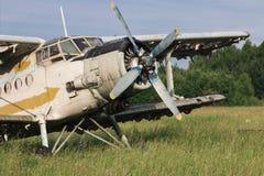 Gammalt flygplan på fältet Arkivbild