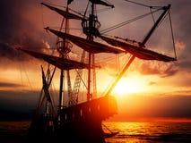 Gammalt forntida piratkopierar skeppet på det fridsamma havet på solnedgången Royaltyfri Bild
