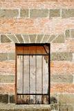 Gammalt gallerförsett fönster på en tegelsten- och stenvägg Royaltyfri Fotografi