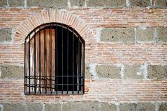 Gammalt gallerförsett fönster på en tegelsten- och stenvägg Arkivfoton