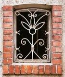 Gammalt gallerförsett fönster på väggen Arkivfoto
