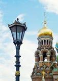 Gammalt gataljus bredvid kupol av templet av frälsaren på blod Arkivbild