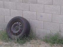 Gammalt gummihjul som lutar upp mot en grå tegelstenvägg royaltyfria foton