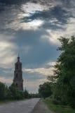 Gammalt högt klockatorn som står vid vägen Royaltyfri Bild