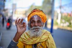 Gammalt hinduiskt helgon som ler för ett foto arkivfoton
